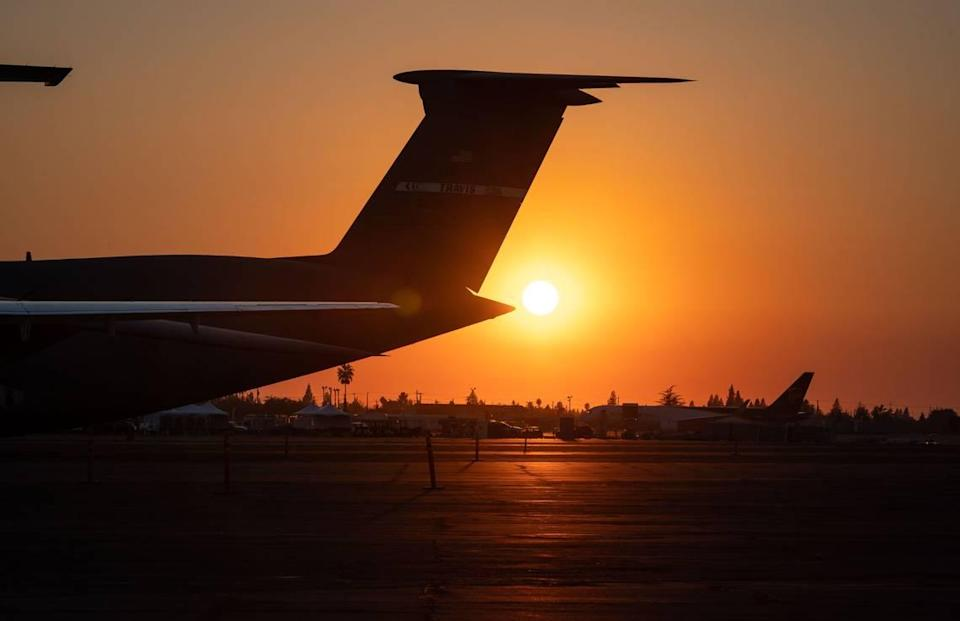 An Air Force C-5M Super Galaxy, left, out of Travis Air Force Base, sits with other planes at Mather Airport at sunset as the first day of the three-day California Capital Airshow wraps up Friday, Sept. 24, 2021, in Sacramento.