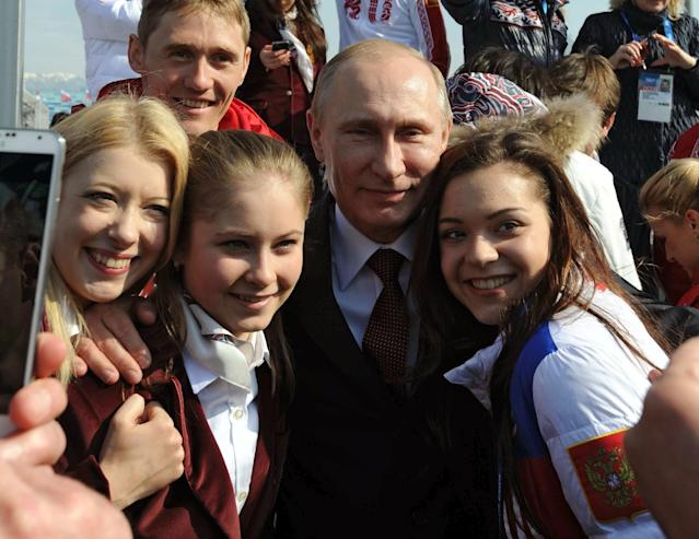 In this photo taken Monday, Feb. 24, 2014 Russian President Vladimir Putin, center, poses with Russian Olympic medal winners after Sochi 2014 Winter Olympics in Sochi, Russia. From left, figure skater Ekaterina Bobrova, cross-country sprinter Nikita Kruikov, back, figure skater Julia Lipnitskaia, and at right, figure skater Adelina Sotnikova. (AP Photo/RIA Novosti Kremlin, Mikhail Klimentyev, Presidential Press Service)