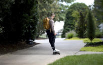 Carolina Panthers running back Christian McCaffrey rides a skateboard down a path at NFL football training camp, Tuesday, July 27, 2021, at Wofford College in Spartanburg, S.C. (Jeff Siner/The Charlotte Observer via AP)