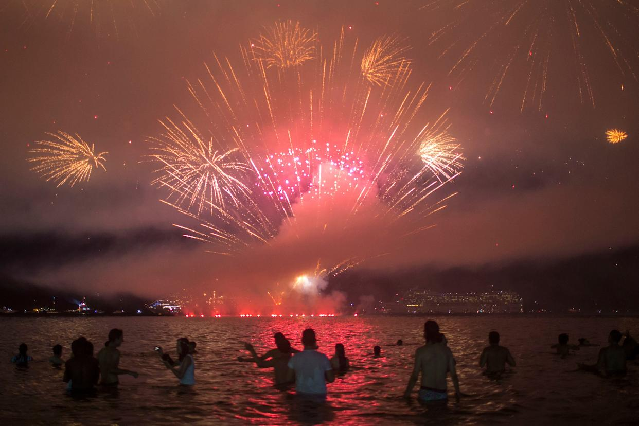 People watch fireworks during New Year's celebrations at Copacabana beach in Rio de Janeiro on January 1, 2018. (Photo: MAURO PIMENTEL via Getty Images)