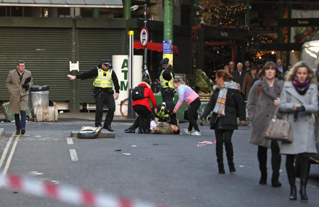 A person is assisted after falling when police evacuated people from Borough Market (AP)