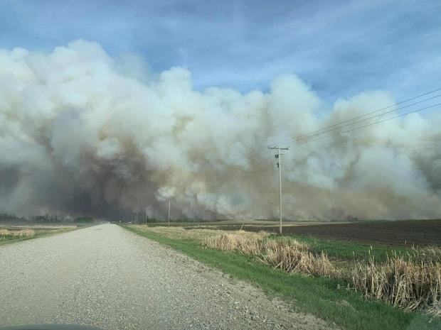 This photo from Wednesday shows smoke from the Cloverdale fire billowing across a grid road northeast of Prince Albert.