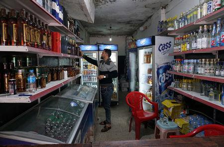 A man displays liquor in the shop, after it was banned during the Islamic State militants' seizure of the city, in Mosul, Iraq April 20, 2019. REUTERS/Abdullah Rashid