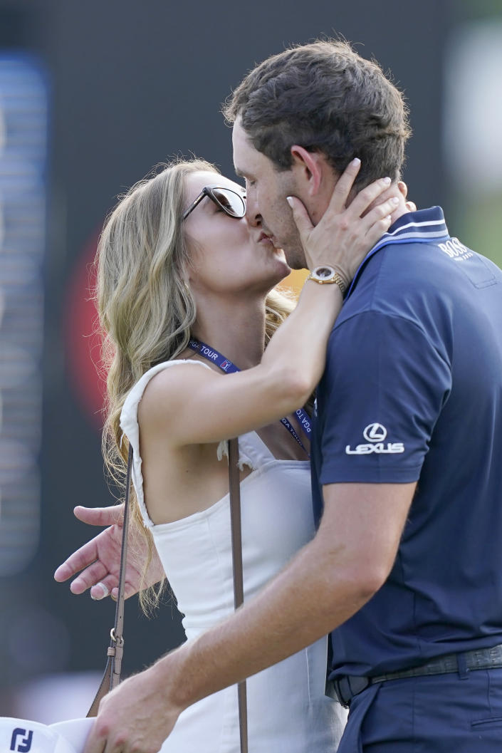 Patrick Cantlay gets a kiss from his girlfriend Nikki Guidish after winning the Tour Championship golf tournament and the FedEx Cup at East Lake Golf Club, Sunday, Sept. 5, 2021 in Atlanta. (AP Photo/Brynn Anderson)