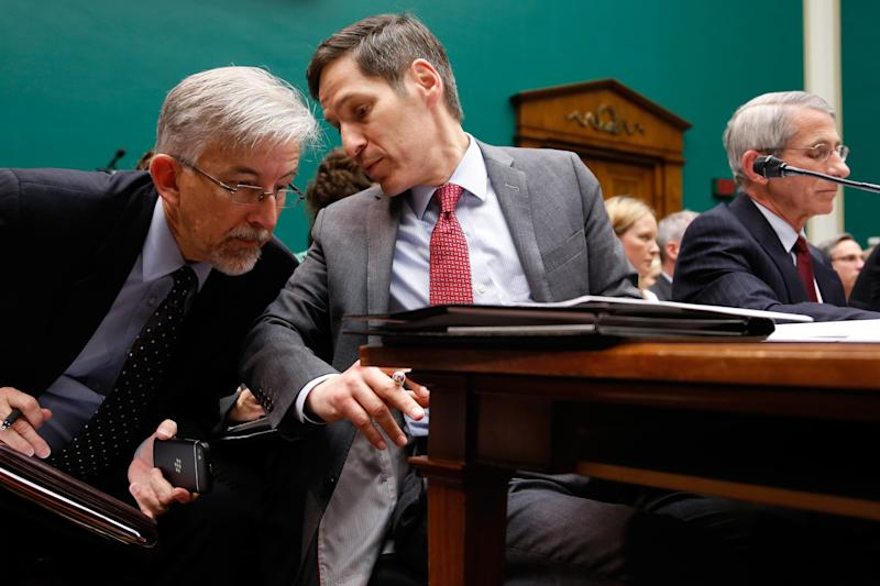 Centers for Disease Control and Prevention Director Tom Frieden (C) speaks with a staff member as he and National Institute of Allergy and Infectious Disease Director Anthony Fauci (R) testify before a House Energy and Commerce Oversight and Investigations Subcommittee hearing on the U.S. response to the Ebola crisis, in Washington October 16, 2014.  REUTERS/Jonathan Ernst    (UNITED STATES - Tags: POLITICS HEALTH)