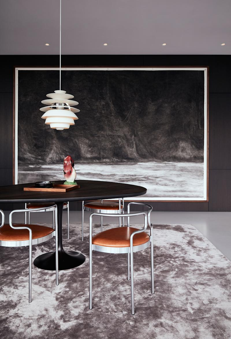 The dining room is backed by a dark-painted American walnut wall to avoid glare in the panoramic glass façade. The wall is designed around the large charcoal drawing by Rotterdam-based artist Renie Spoelstra. The dining table, on a Saarinen Tulip base above a Wool Studio carpet, is custom; the chairs are by Henning Larsen for Fritz Hansen, 1980s.