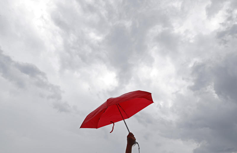 A pro-China supporter holds a red umbrellas during a counter-rally in support of the police in Hong Kong Saturday, July 20, 2019. Police in Hong Kong have raided a homemade-explosives manufacturing lab ahead of another weekend of protests in the semi-autonomous Chinese territory. (AP Photo/Vincent Yu)