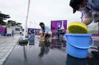 Volunteers attempt to remove the rainwater from the range before the women's trap practice at the Asaka Shooting Range in the 2020 Summer Olympics, Tuesday, July 27, 2021, in Tokyo, Japan. (AP Photo/Alex Brandon)