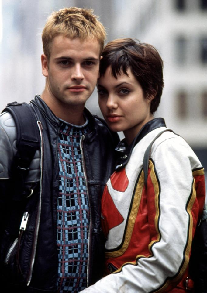 "Golden Globe winner Angelina Jolie married her first husband, Jonny Lee Miller, after the two worked on ""Hackers."" When they wed on March 28, 1996, she wore black rubber pants with Miller's name written in blood. However, things with Miller cooled by 1997, and the two separated in September. (Photo from ""Hackers"",1995)"