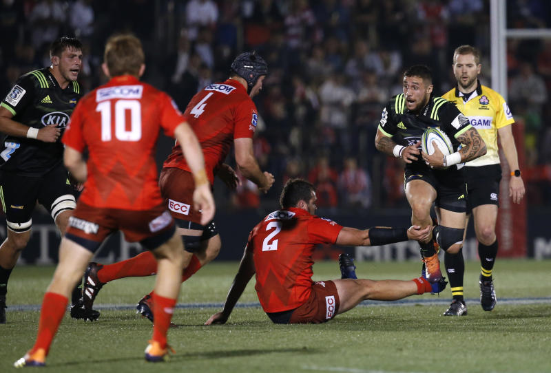 Hurricane's TJ Perenara, right, runs at Sunwolves defense during the Super Rugby game between the Hurricanes and Sunwolves in Tokyo, Friday, April 19, 2019. (AP Photo/Shuji Kajiyama)