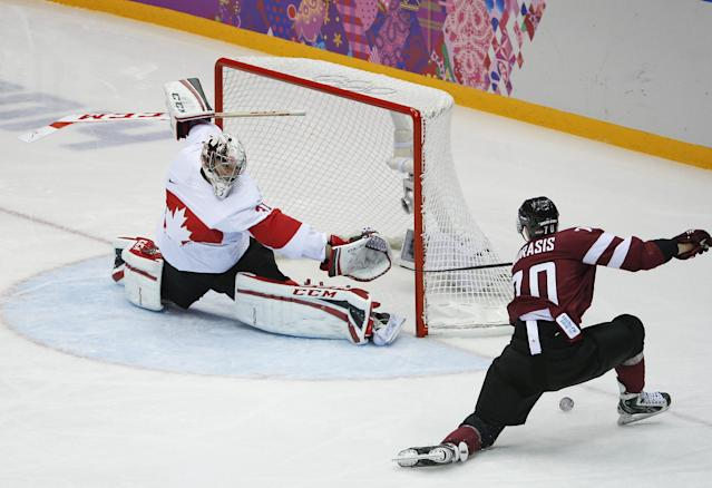 Canada goaltender Carey Price blocks a shot by Latvia forward Miks Indrasis during the second period of a men's quarterfinal ice hockey game at the 2014 Winter Olympics, Wednesday, Feb. 19, 2014, in Sochi, Russia. (AP Photo/Mark Humphrey)
