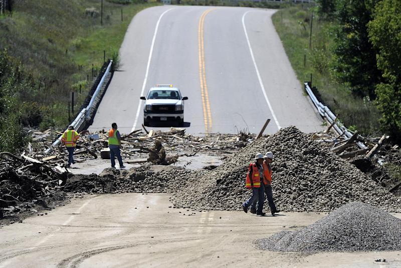FILE- In this Sept. 18, 2013, file photo, workers walk by a damaged bridge on Highway 34 over the Big Thompson River near Loveland, Colo., on Wednesday, Sept. 18, 2013. Colorado transportation officials are scrambling to replace key mountain highways with at least gravel before the first winter storms hit as early as October, but rebuilding every flood-damaged road and bridge in the mountains and plains will have to wait until 2014 _ or beyond. (AP Photo/Chris Schneider, File)