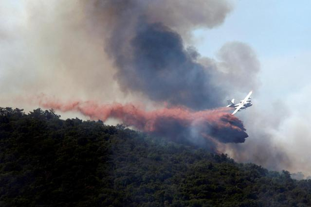 <p>Smoke fills the sky as a plane drops flame retardant on a burning hillside in Bormes-les-Mimosas, in the Var department, France, July 26, 2017. (Jean-Paul Pelissier/Reuters) </p>