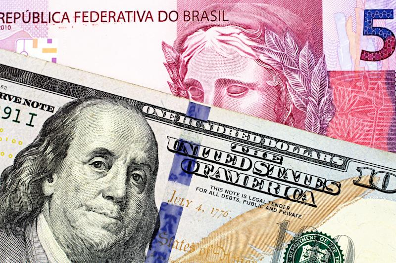 A macro image of a pink five Brazilian reais bank note with a close up image of a blue, one hundred American dollar bill close up