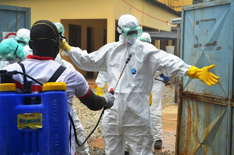 Guinea's Red Cross health workers prepare to carry the body of a victim at the MSF Ebola treatement centre near the hospital in Conakry on September 14, 2014