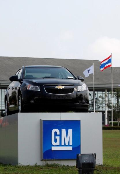 FILE PHOTO: The Thai national flag and a car are displayed vehicle in front of the General Motors (GM) plant in the Eastern Seaboard Industrial Estate in Rayong province February 22, 2011