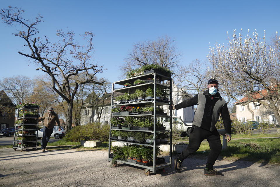 Staff members of a flower shop drag merchandise carts in Budapest, Hungary, Wednesday April 7, 2021. Hungary's government lifted several lockdown restrictions on Wednesday, even as some doctors and medical experts urged caution after a record-breaking day of COVID-19 deaths, a move that came as Hungary reached 2.5 million first-dose vaccinations, a benchmark the government set for when a gradual reopening could move forward. (AP Photo/Laszlo Balogh)