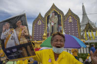 Supporters of the monarchy display images of King Maha Vajiralongkorn and Queen Suthida as they gather in front of the Grand Place in Bangkok, Thailand, Sunday, Nov. 1, 2020. Hundreds of royalists gathered close to the Grand Palace in which King Maha Vajiralongkorn is scheduled to visit for a Buddhist religious ceremony. (AP Photo/Wason Wanichakorn)