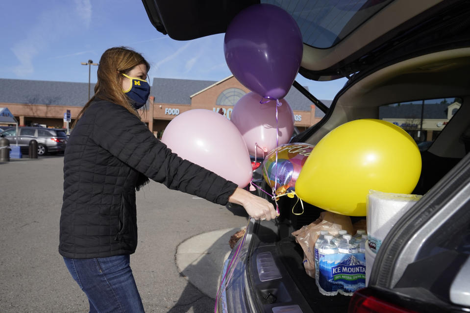 Volunteer Erica Stowe packs groceries and balloons into her vehicle, Thursday, Nov. 19, 2020, in Ann Arbor, Mich. A group of parents has come together to help support University of Michigan students while they are sick or quarantining. The group of mostly moms was started and is organized by Sherry Levine of Rye Brook, New York, who's also a mother of a Michigan student. After she spread the word on parent pages on Facebook, local volunteers stepped up to help fulfill student requests by dropping off groceries or supplies. (AP Photo/Carlos Osorio)