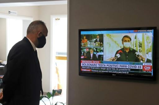 A funeral home worker in Curitiba watches the live news as President Jair Bolsonaro announces his positive COVID-19 test result