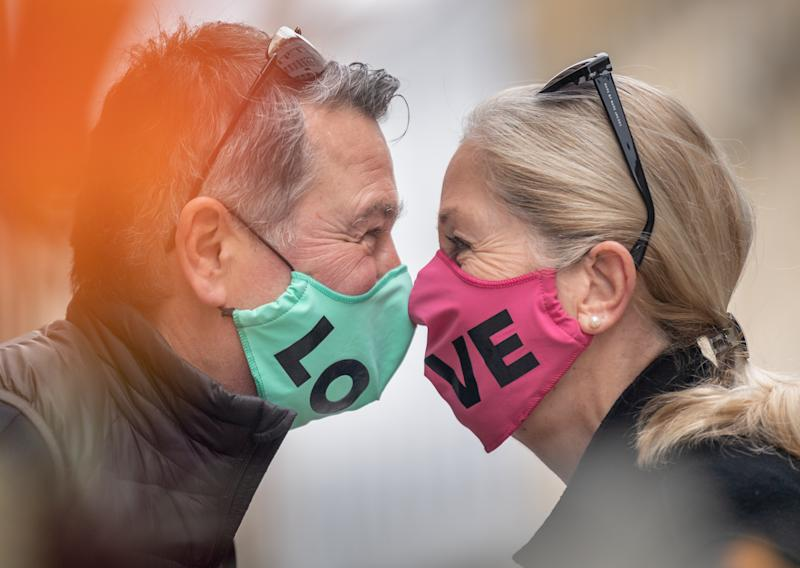 "27 April 2020, Bavaria, Munich: Jörg and Petra wear their face masks with the word ""Love"" sewn on the front. From this week on, shops with up to 800 square meters of sales space in Bavaria will be allowed to reopen under certain conditions. However, a strict mouth and nose protection obligation applies in shops and on public transport. Photo: Peter Kneffel/dpa (Photo by Peter Kneffel/picture alliance via Getty Images)"