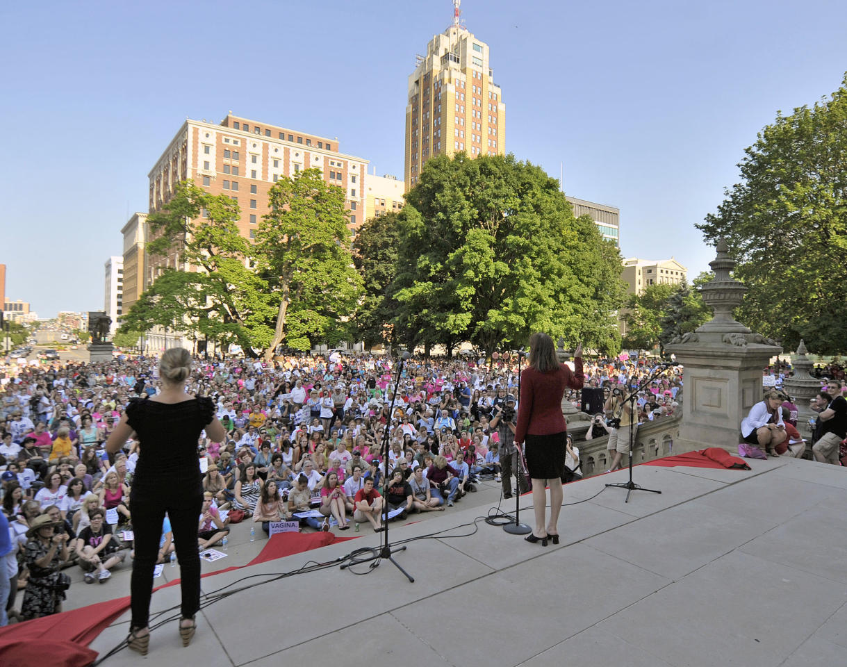 "Rep Lisa Brown, D-West Bloomfield, center, addresses supporters who gather for her performance of ""The Vagina Monologues"" with 10 other lawmakers and several actresses on the Michigan Statehouse steps, Monday, June 18, 2012, in Lansing, Mich. Brown, who says she was barred from speaking in the Michigan House because Republicans objected to her saying ""vagina"" during debate over anti-abortion legislation, performed ""The Vagina Monologues"" with a hand from the author Eve Ensler. (AP Photo/Detroit News, Dale G. Young)"
