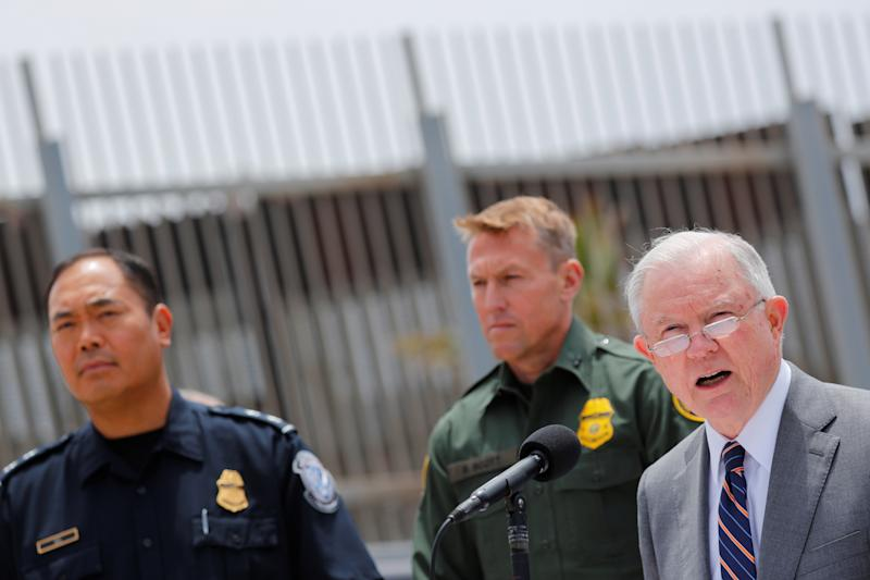 "U.S. Attorney General Jeff Sessions holds a news conference next to the U.S.-Mexico border in San Diego to discuss immigration enforcement actions on May 7. A month earlier, he announced the administration's ""zero tolerance"" policy. (Mike Blake / Reuters)"