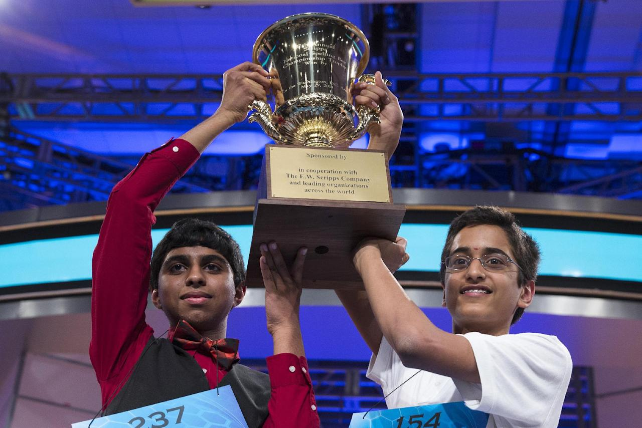 Ansun Sujoe, 13, left, of Fort Worth, Texas, and Sriram Hathwar, 14, of Painted Post, N.Y., raise the championship trophy after being named co-champions of the Scripps National Spelling Bee, on Thursday, May 29, 2014, in Oxon Hill, Md. (AP Photo/ Evan Vucci)