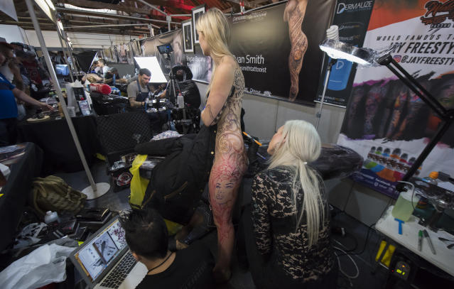 <p>A young woman has her body tattooed at the London Tattoo convention at Tobacco Dock on Sept. 23, 2017 in London, England. (Photo: James D. Morgan/Getty Images) </p>