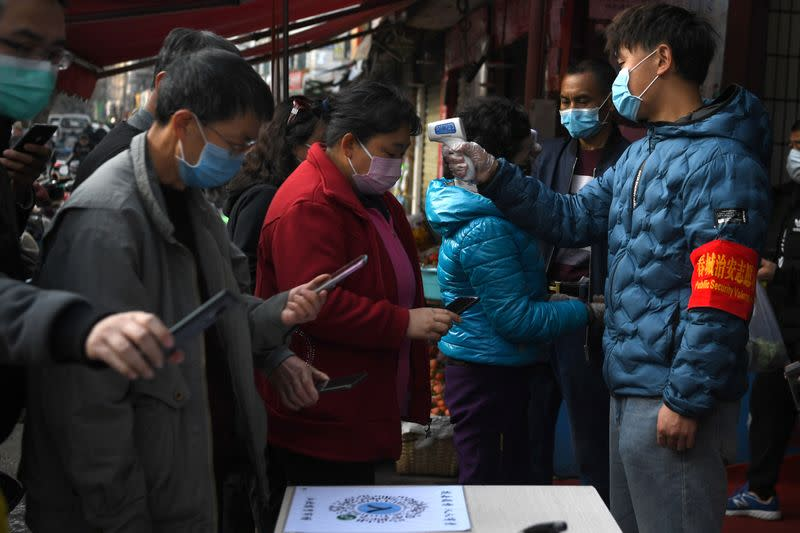 People wearing face masks scan a QR code to submit their personal information while security volunteers check their temperatures at an entrance of a grocery market, as the country is hit by an outbreak of the novel coronavirus, in Kunming