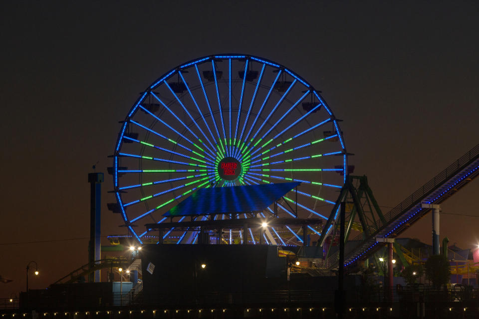 Pacific Park's solar-powered Ferris wheel lights show a green