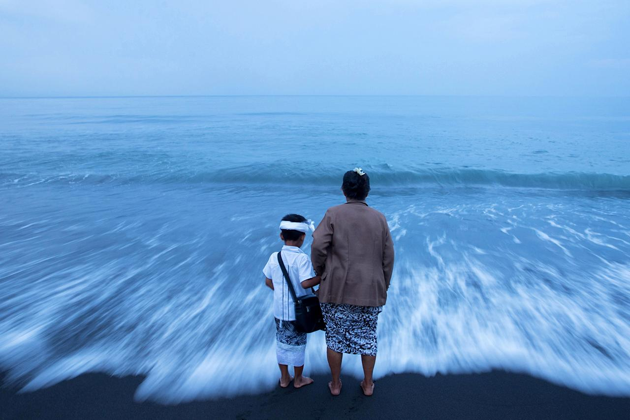 <p>A Balinese Hindu woman hold her grandson's hand on a beach during Melasti, a purification ceremony ahead of the holy day of Nyepi, in Gianyar, Bali, Indonesia March 25, 2017. (Photo: Agung Parameswara/Reuters) </p>