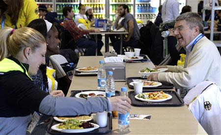 International Olympic Committee (IOC) President Thomas Bach (R) laughs as he eats lunch with athletes in the coastal Athlete's Village at the Sochi 2014 Winter Olympics February 1, 2014. REUTERS/Pascal Le Segretain/Pool