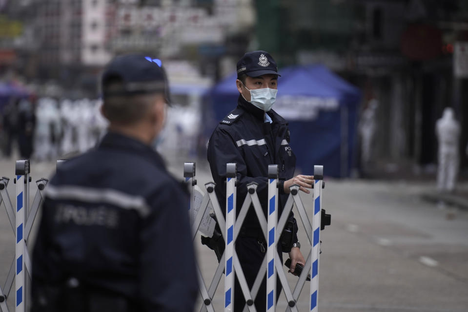 Police officers stand guard at the closed area in Jordan district, in Hong Kong, Sunday, Jan. 24, 2021. Thousands of Hong Kong residents were locked down Saturday in an unprecedented move to contain a worsening outbreak in the city, authorities said. (AP Photo/Vincent Yu)