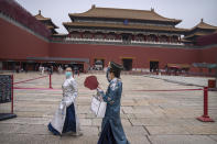 Visitors in historical dress and wearing face masks to protect against COVID-19 walk near the entrance to the Forbidden City in Beijing, Saturday, Sept. 18, 2021. (AP Photo/Mark Schiefelbein)