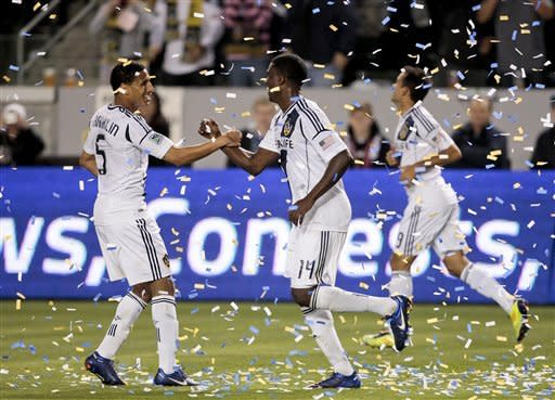 Los Angeles Galaxy forward Edson Buddle, middle, celebrates scoring a goal with Los Angeles Galaxy defender Sean Franklin, left, during the second half of an MLS soccer match, Saturday, March 10, 2012, in Carson, Calif. Real Salt Lake won 3-1.(AP Photo/Bret Hartman)