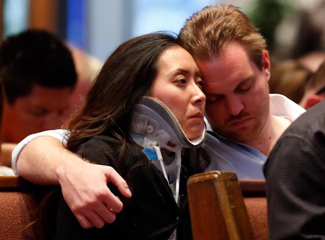 MOORE, OK - MAY 26: (L-R) Plaza Towers Elementary School teacher Jennifer Doan is comforted by her fiance, Nyle Rogers, during the Oklahoma Strong memorial service held to honor victims of the recent deadly tornado at the First Baptist Church on May 26, 2013 in Moore, Oklahoma. The tornado of EF5 strength and two miles wide touched down May 20 killing at least 24 people and leaving behind extensive damage to homes and businesses. U.S. President Barack Obama visited the area Sunday and promised federal aid to supplement state and local recovery efforts. (Photo by Sue Ogrocki-Pool/Getty Images)