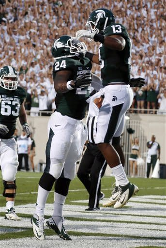 Michigan State's Le'Veon Bell (24) and Bennie Fowler (13) celebrate Bell's first-quarter touchdown against Boise State in an NCAA college football game, Friday, Aug. 31, 2012, in East Lansing, Mich. (AP Photo/Al Goldis)