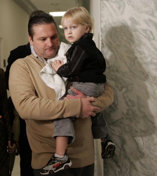 IFLE - This Feb. 1, 2008 file photo shows former major league baseball player Chuck Knoblauch, holdings his son Jake on Capitol Hill in Washington, following his deposition before the House Oversight and Government Reform Committee. The key witness in the Roger Clemens perjury trial testified Monday, May 21, 2012 about three other baseball players who he said took human growth hormone. Brian McNamee, Clemens' longtime strength and conditioning coach, told jurors that he provided HGH to current Yankee pitcher Andy Pettitte and former Yankee infielder Chuck Knoblauch. McNamee also testified that former Yankee pitcher Mike Stanton obtained HGH from drug dealer Kirk Radomski, after McNamee put them in touch.(AP Photos/Susan Walsh)