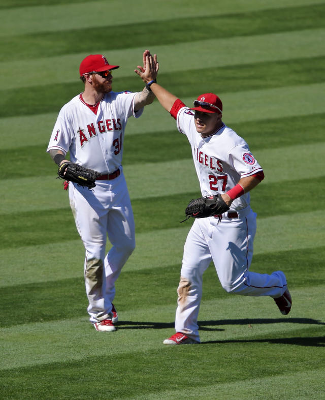 Los Angeles Angels' Josh Hamilton, left, and Mike Trout celebrate after the defeated the Oakland Athletics 8-1 in a baseball game, Sunday, Aug. 31, 2014, in Anaheim, Calif. (AP Photo/Mark J. Terrill)