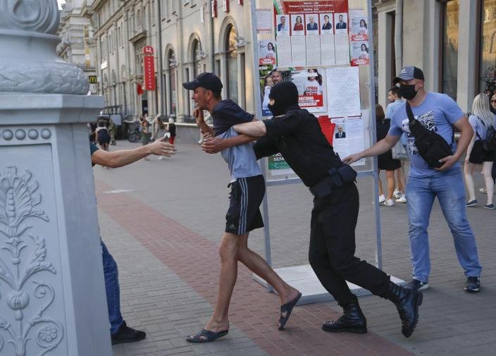 Belarusian police officers detain a man in Minsk, Belarus, Saturday, Aug. 8, 2020. On Saturday evening, police arrested at least 10 people as hundreds of opposition supporters drove through the center of the capital waving flags and brandishing clenched-fist victory signs from the vehicles' windows. The presidential election in Belarus is scheduled for August 9, 2020. (AP Photo/Sergei Grits)