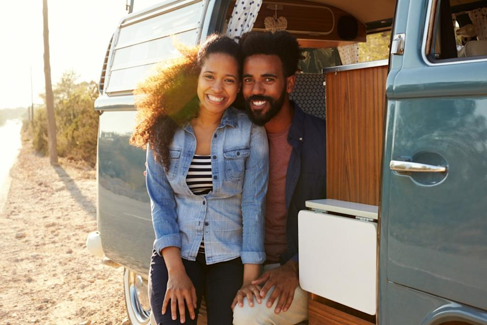 happy young straight black couple sitting in van
