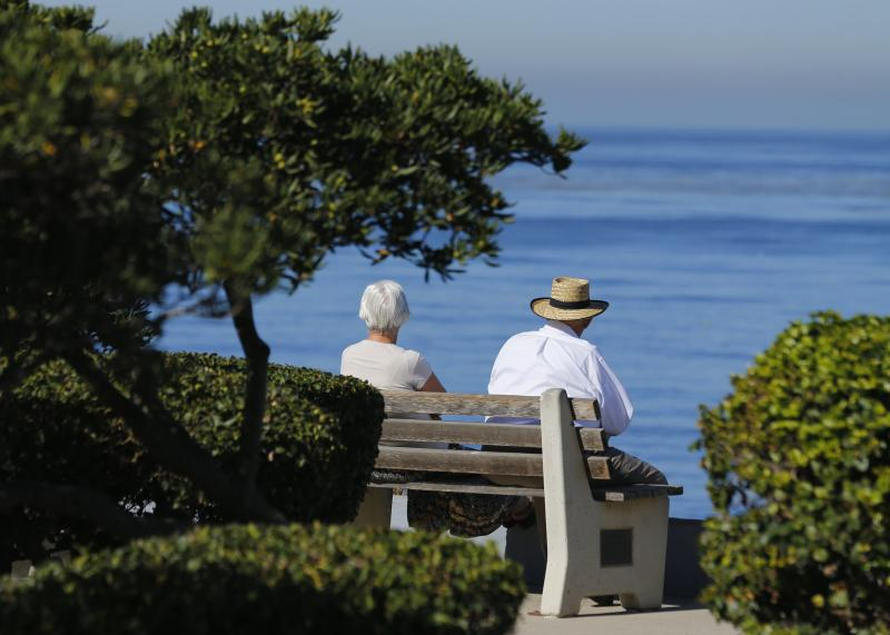 An elderly couple looks out at the ocean as they sit on a park bench in La Jolla, California November 13, 2013. REUTERS/Mike Blake (UNITED STATES - Tags: SOCIETY ENVIRONMENT)