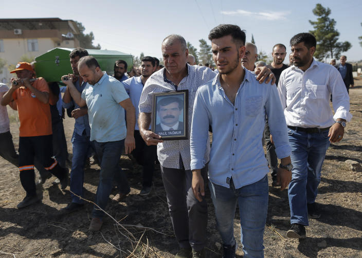Mourners carry the coffin of Halil Yagmur, 64, killed Friday during mortar shelling from Syria, during a funeral procession in the town of Suruc, southeastern Turkey, at the border with Syria, Saturday, Oct. 12, 2019. Turkey's military said it captured a key Syrian border town under heavy bombardment Saturday as its offensive against Kurdish fighters pressed into its fourth day with little sign of relenting despite mounting international criticism. (AP Photo/Emrah Gurel)