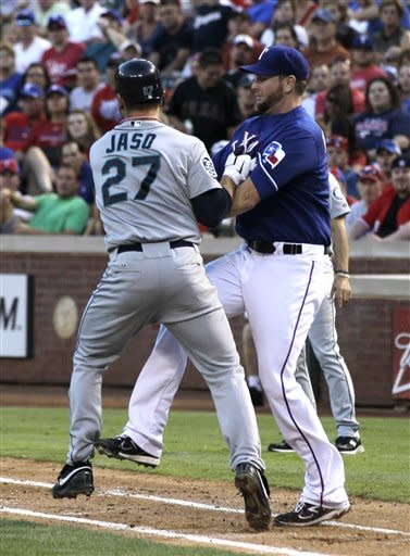 Seattle Mariners' John Jaso (27) is tagged out by Texas Rangers starting pitcher Scott Feldman after Feldman fielded a slow roller up the first base line by Jaso in the fourth inning of a baseball game Tuesday, May 29, 2012, in Arlington, Texas. (AP Photo/Tony Gutierrez)