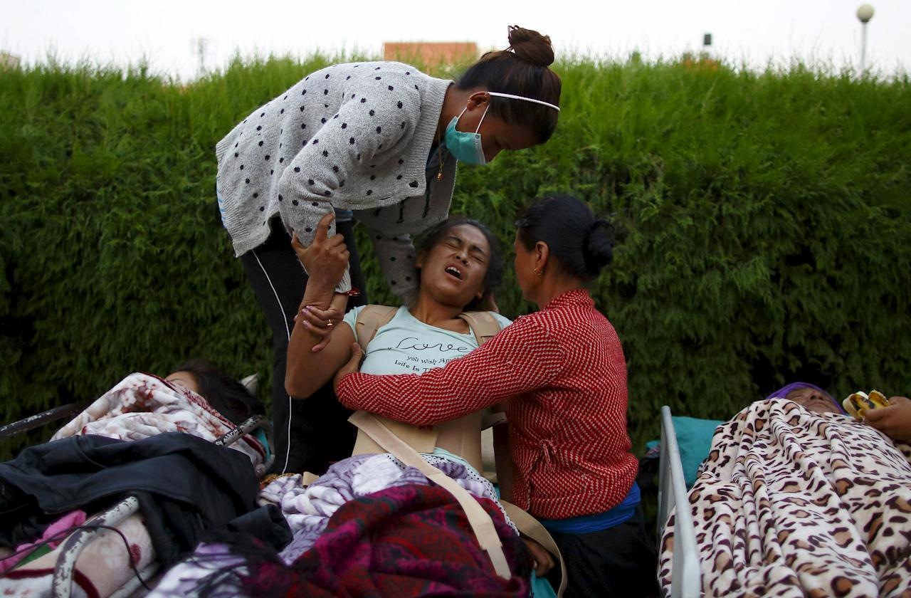 An earthquake victim reacts in pain after being moved out from the hospital to the open ground for treatment, in Kathmandu, May 12, 2015. A 7.3 magnitude earthquake killed at least 37 people and spread panic in Nepal on Tuesday, bringing down buildings already weakened by a devastating tremor less than three weeks ago and unleashing landslides in Himalayan valleys near Mount Everest. The earthquake was centered 76 km (47 miles) east of the capital in a hilly area close to the border with Tibet, according to coordinates provided by the U.S. Geological Survey. REUTERS/Navesh Chitrakar