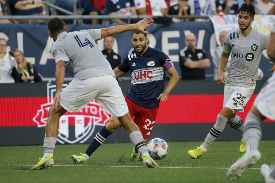 New England Revolution midfielder Carles Gil (22) dribble through the CF Montreal defense during the second half of an MLS soccer match, Sunday, July 25, 2021, in Foxborough, Mass. (AP Photo/Mary Schwalm)