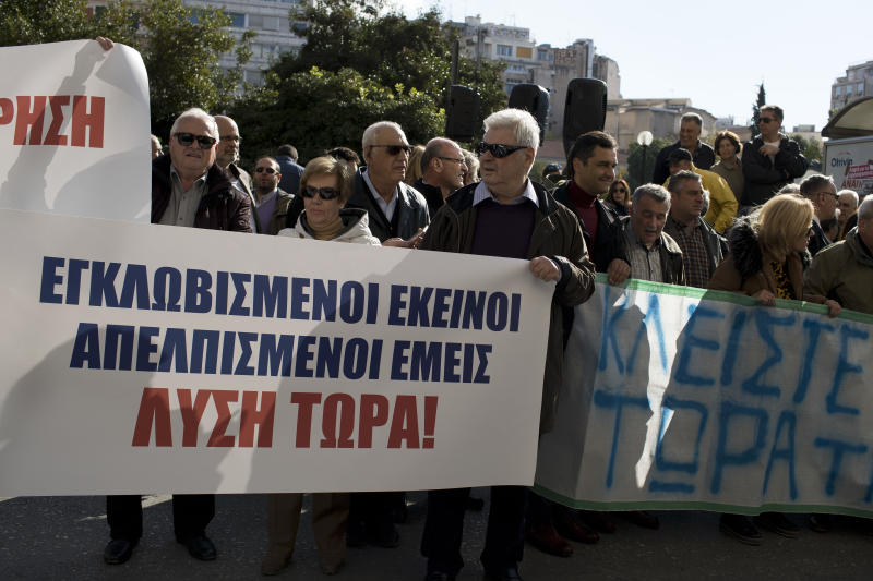"""Residents and Mayors of the island of Lesvos, Chios , and Samos hold a banner as they protest outside the Migration Ministry in central Athens, Tuesday, Dec. 5, 2017. The protesters demonstrated against the increasingly precarious and overcrowded conditions for newly arriving migrants and refugees. The banner on left reads in Greek """" """"they are trapped we are desperate. Solution Now! '' (AP Photo/Petros Giannakouris)"""