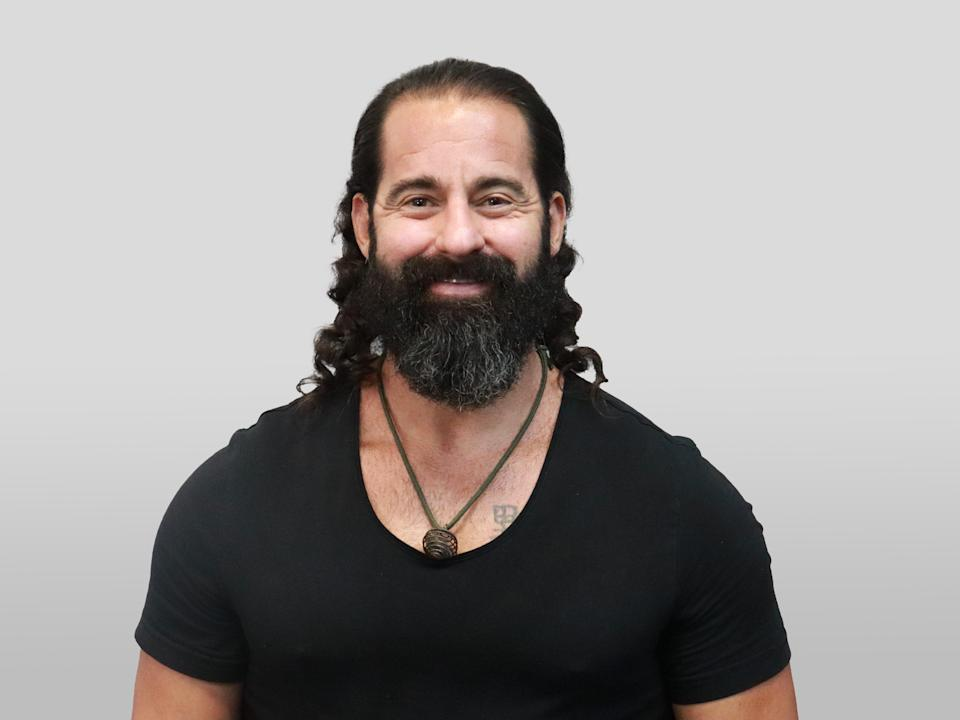 This is a headshot photo of Coach JV. He's wearing a black t-shirt and smiling into the camera.