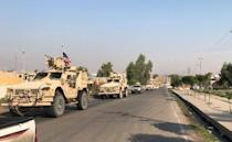 A convoy of U.S. vehicles are seen after withdrawing from northern Syria, at the Iraqi-Syrian border crossing in the Sahela